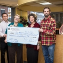 Counseling and Psychological Services Center staff hold up giant check for suicide prevention program